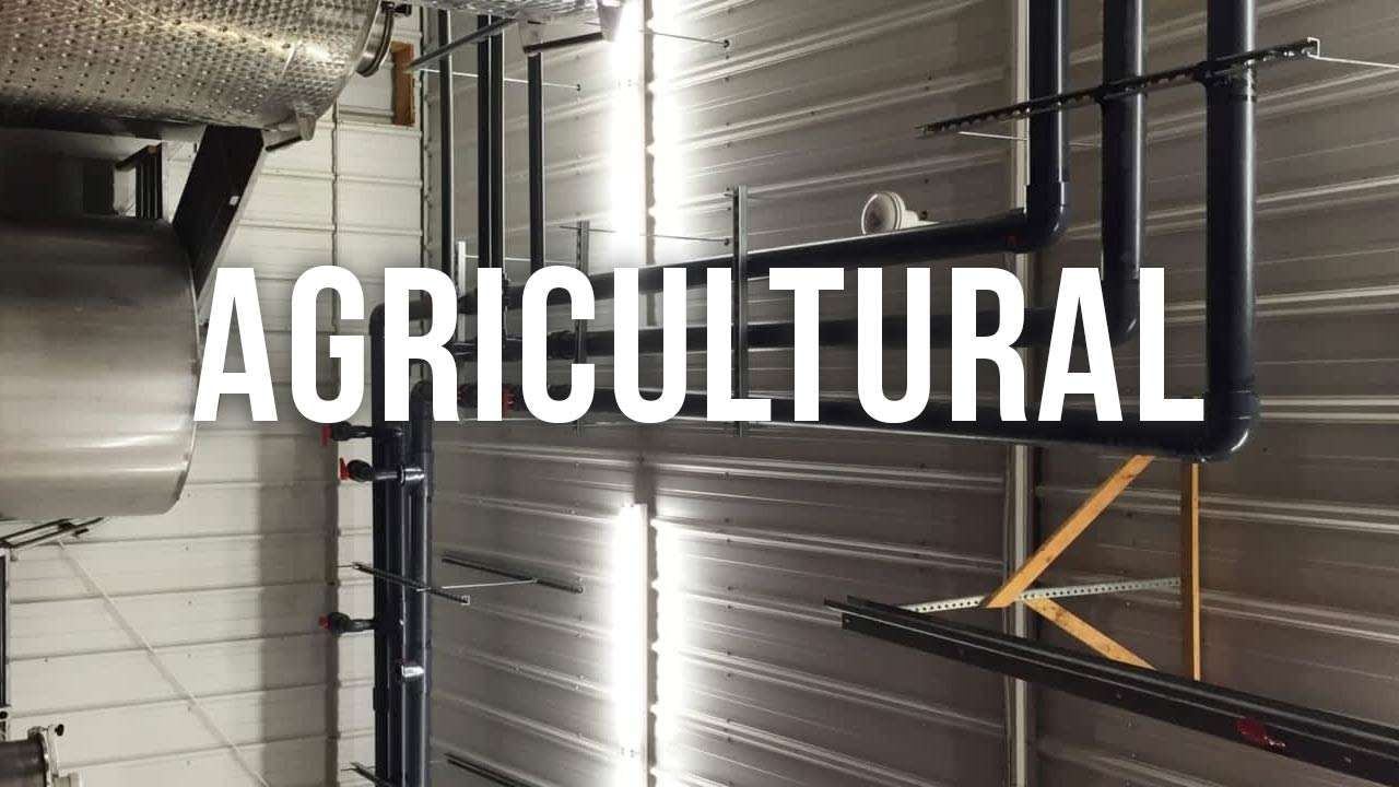 "pvc pipes organized neatly and installed along a metal wall with ""agricultural"" text"