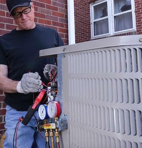 adult installing HVAC outdoors