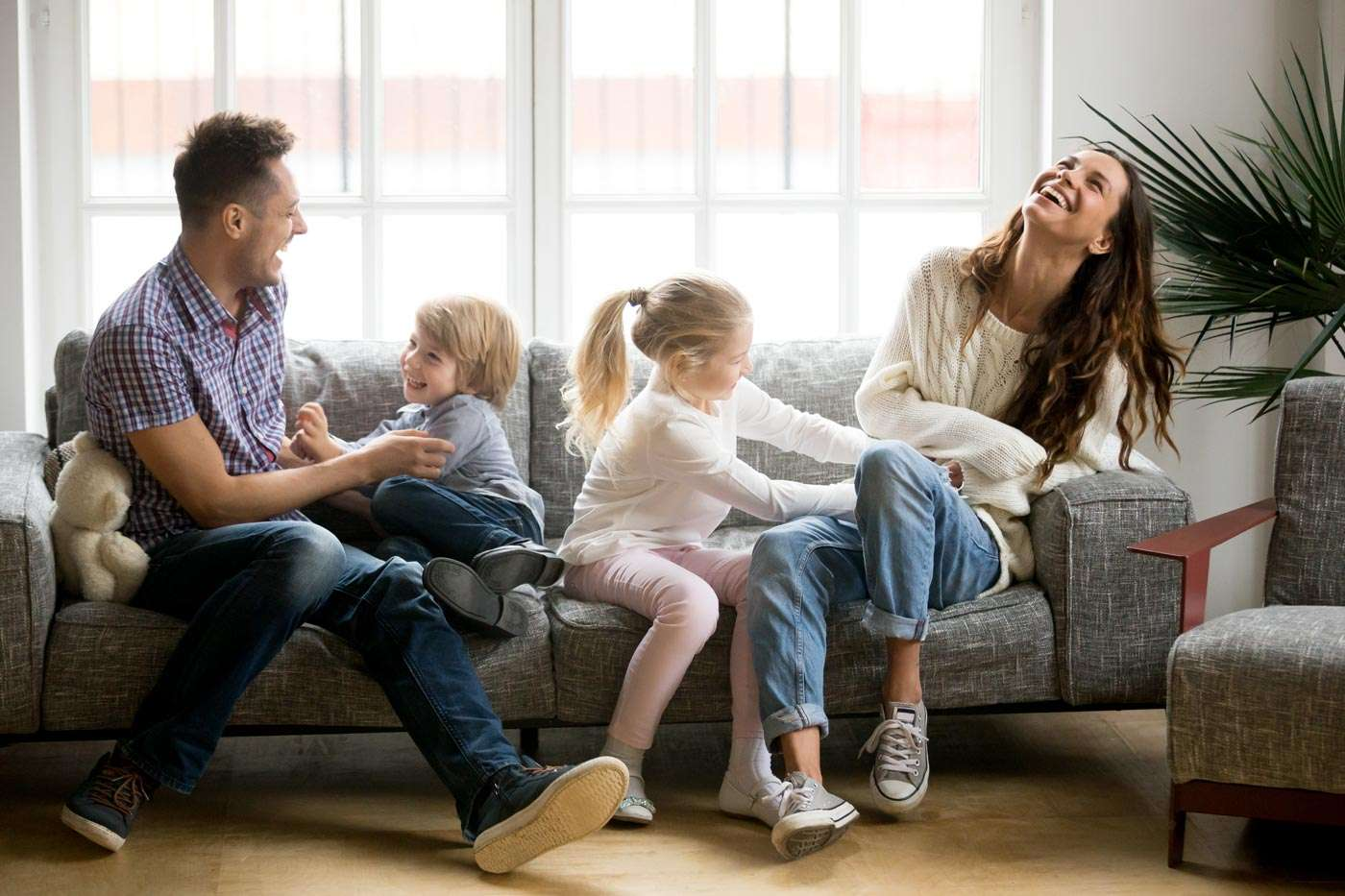 family of four laughing on a couch