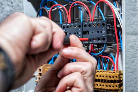 A picture of a mechanic working on an electrical panel.